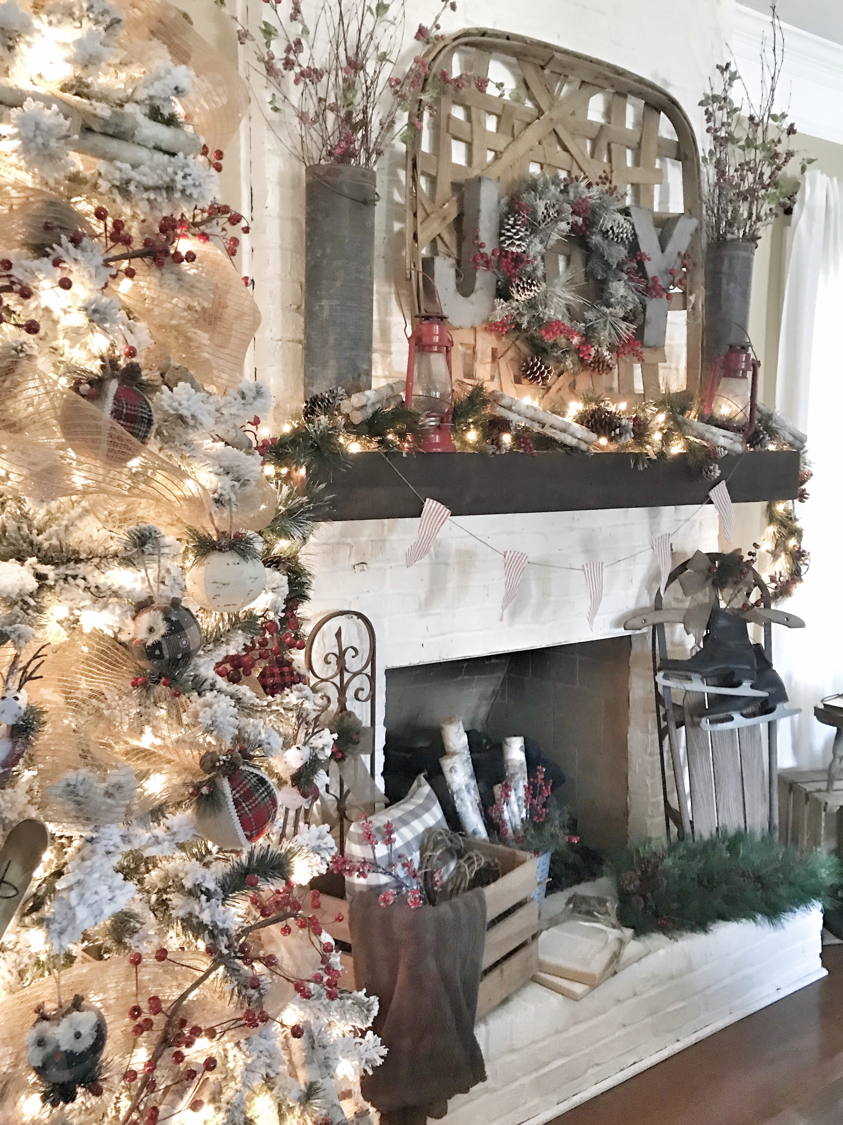flocked Christmas tree and fireplace with Christmas decor