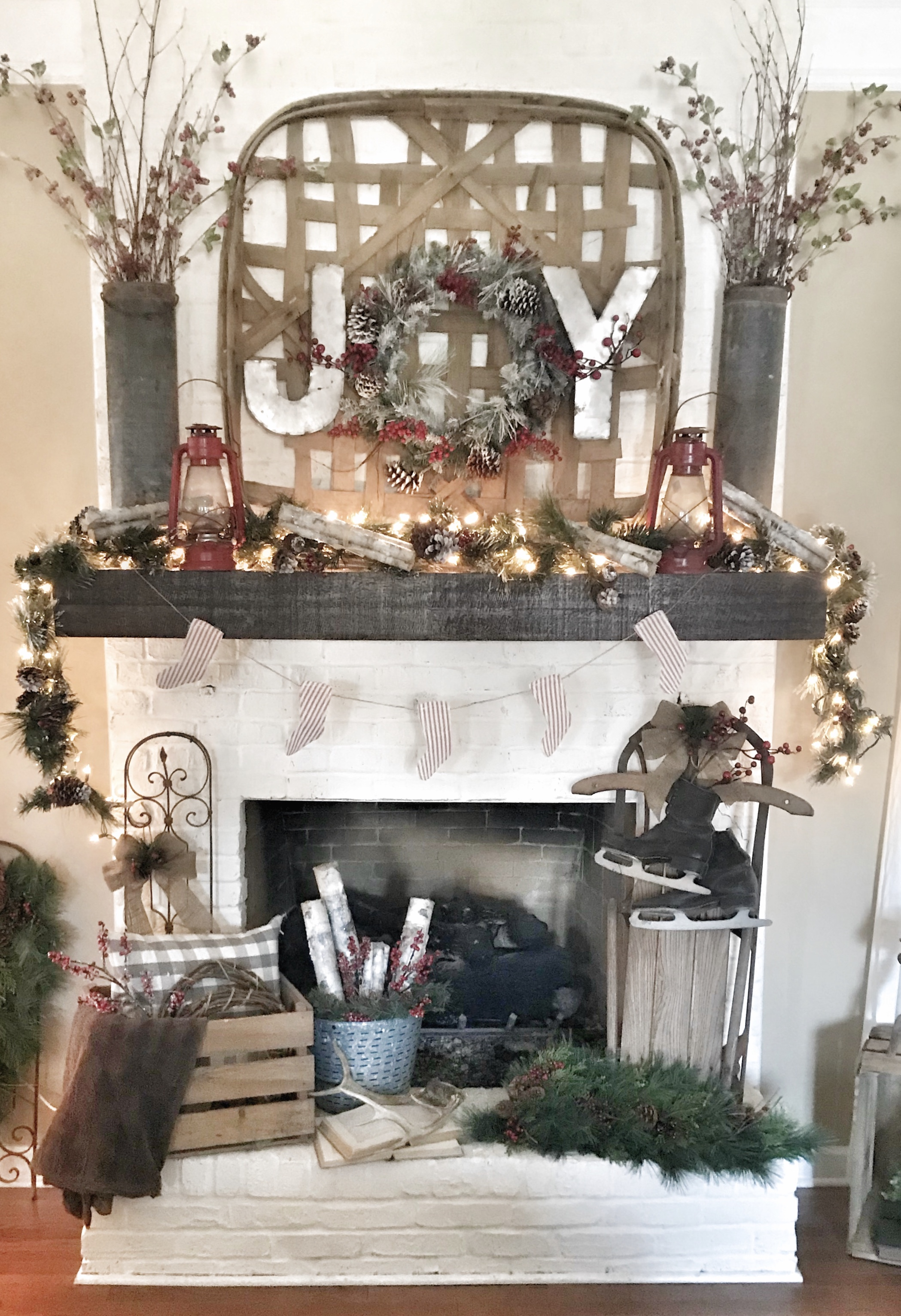 mantel decorated for Christmas with garland, lights, and joy sign