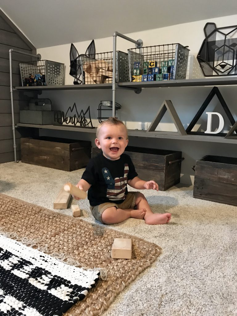 baby playing in front of shelves