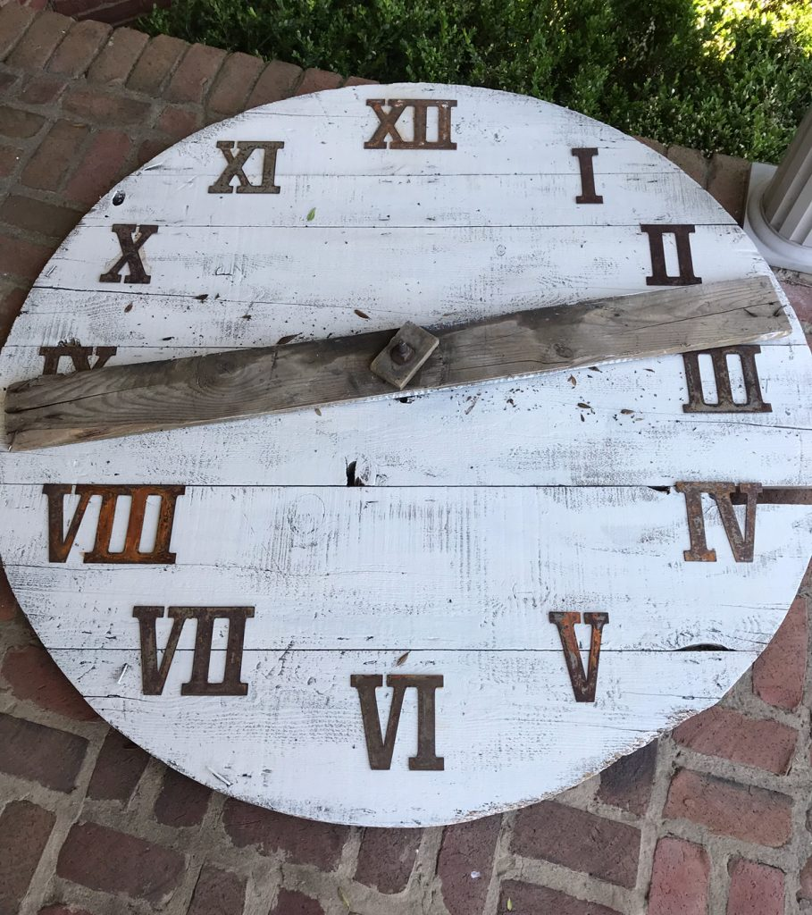 wooden clock painted white with roman numerals
