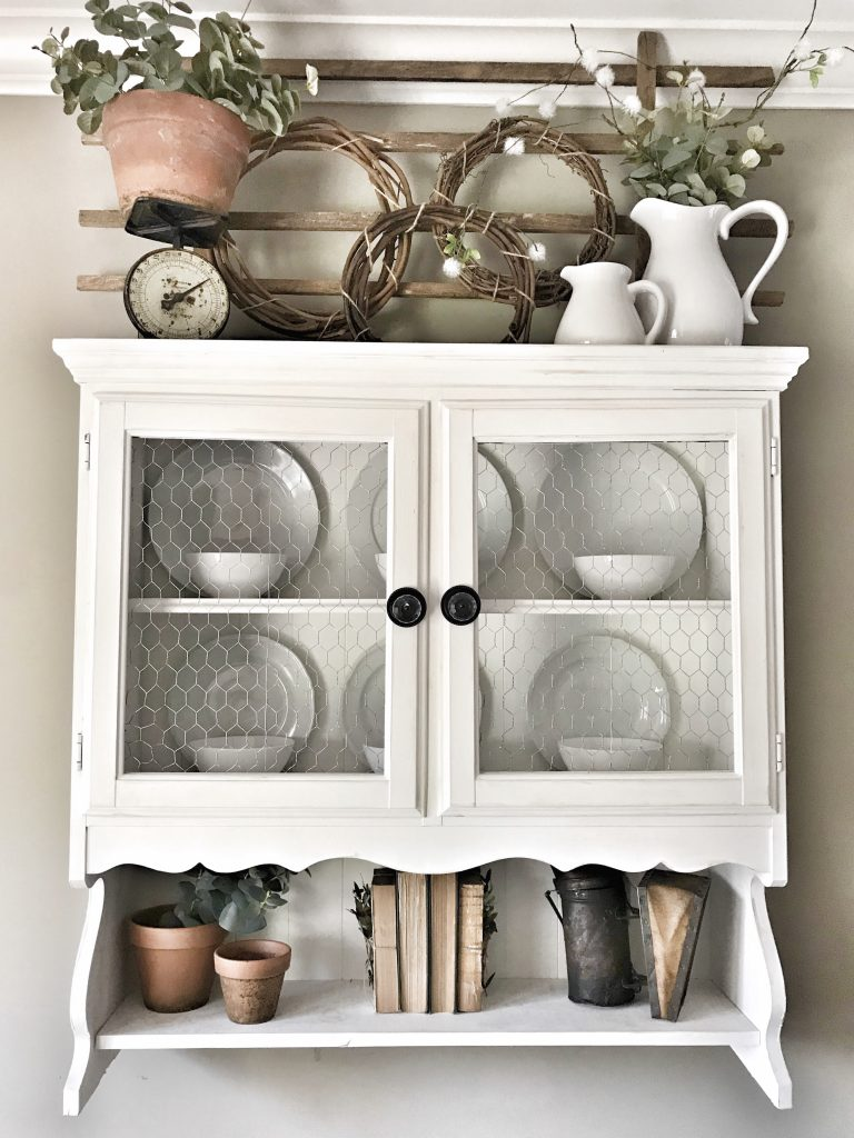 hanging hutch with greenery and clay pots