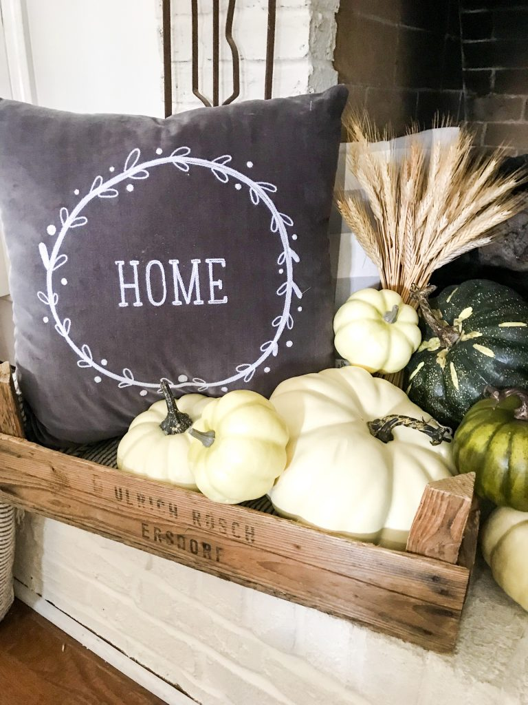 vintage crate with pillows and green and white pumpkins