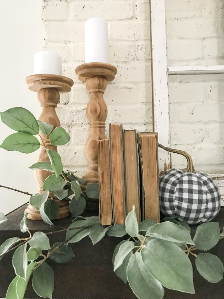 mantel with candlesticks pumpkins books and greenary