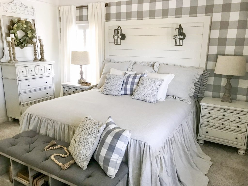 white bed with plaid wallpaper