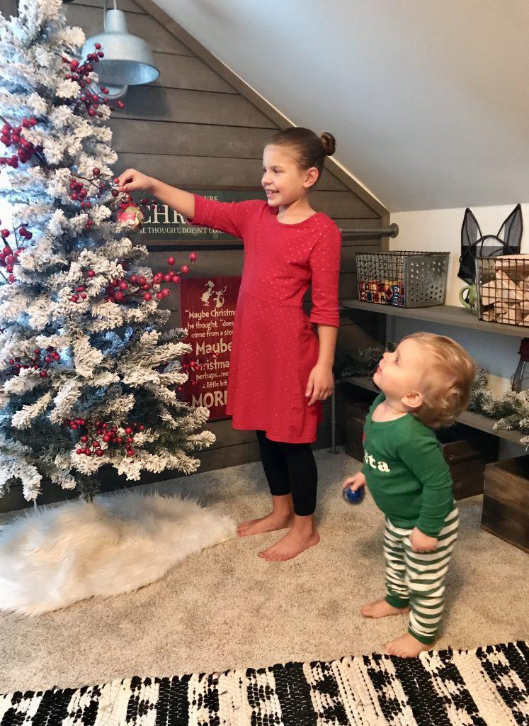 children hanging Grinch Christmas ornament