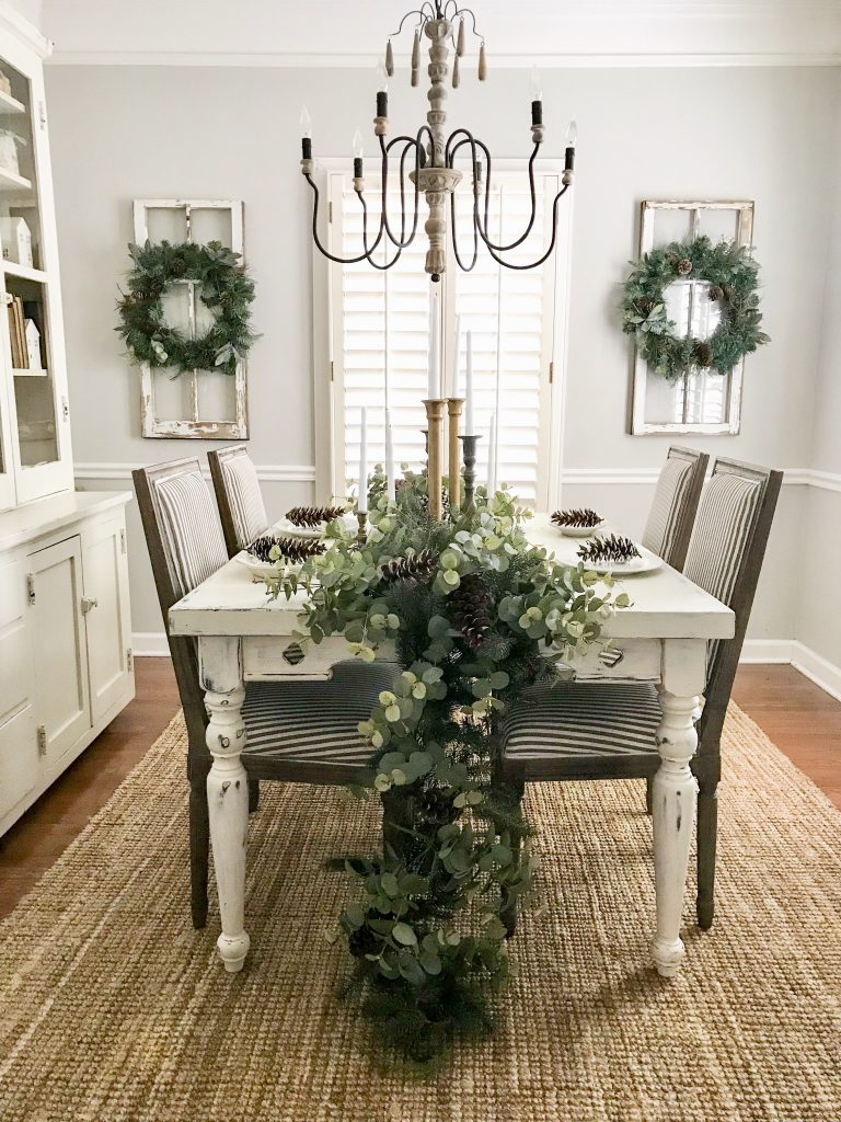 dining room with greenery and candlesticks