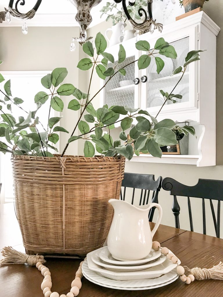 basket with greenery and white pitcher
