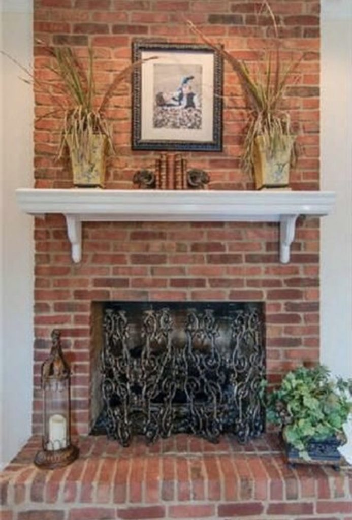 red brick fireplace with white mantel