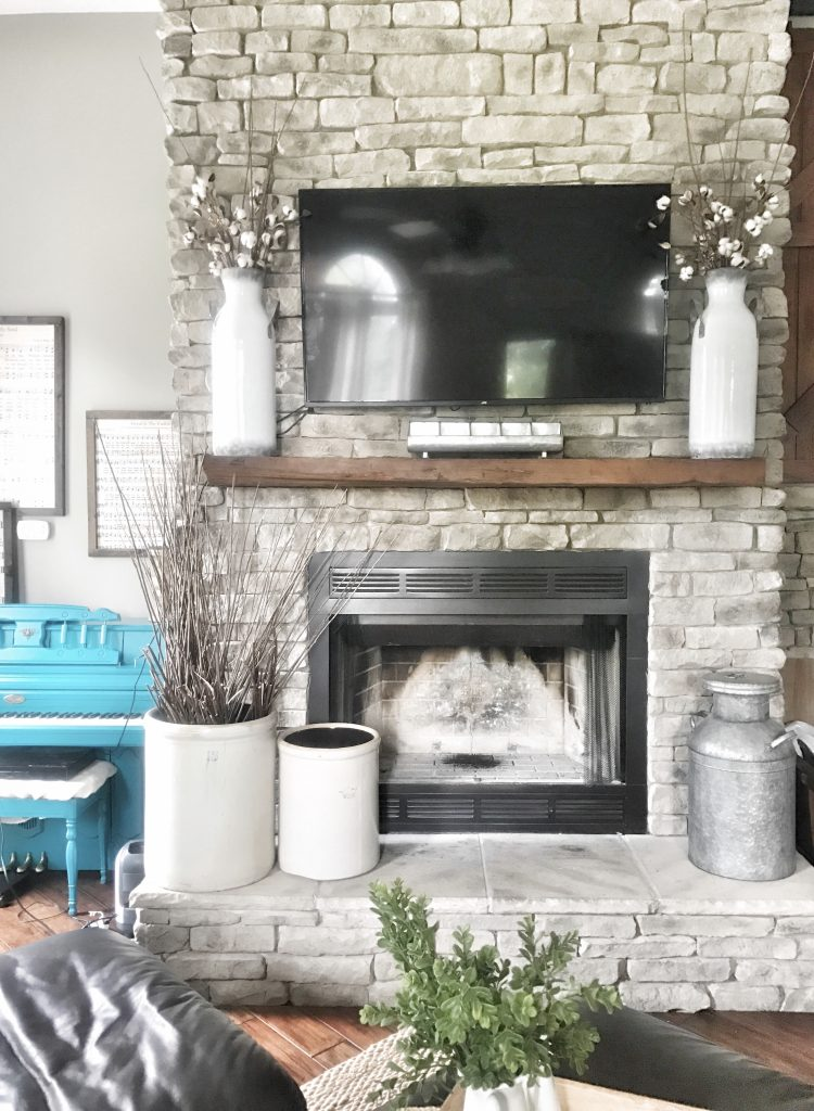 stone fireplace redecorated with crocks and jugs