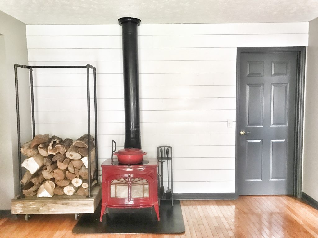 shiplap wall with red stove and wood