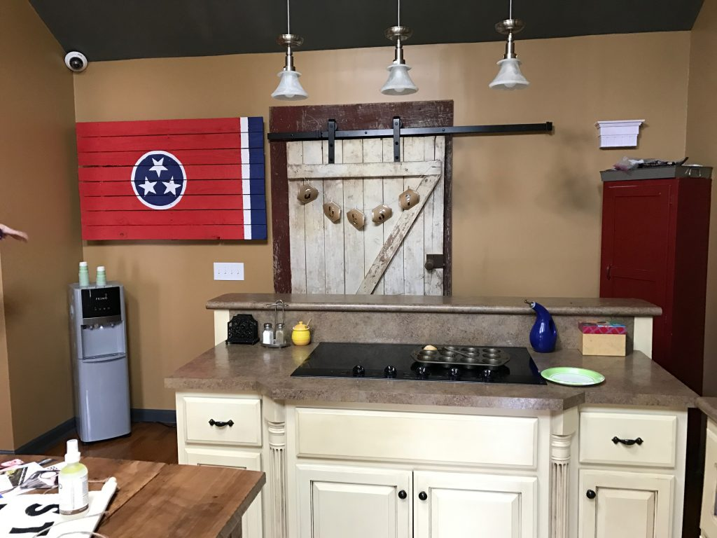 cluttered kitchen area with wooden Tennessee flag