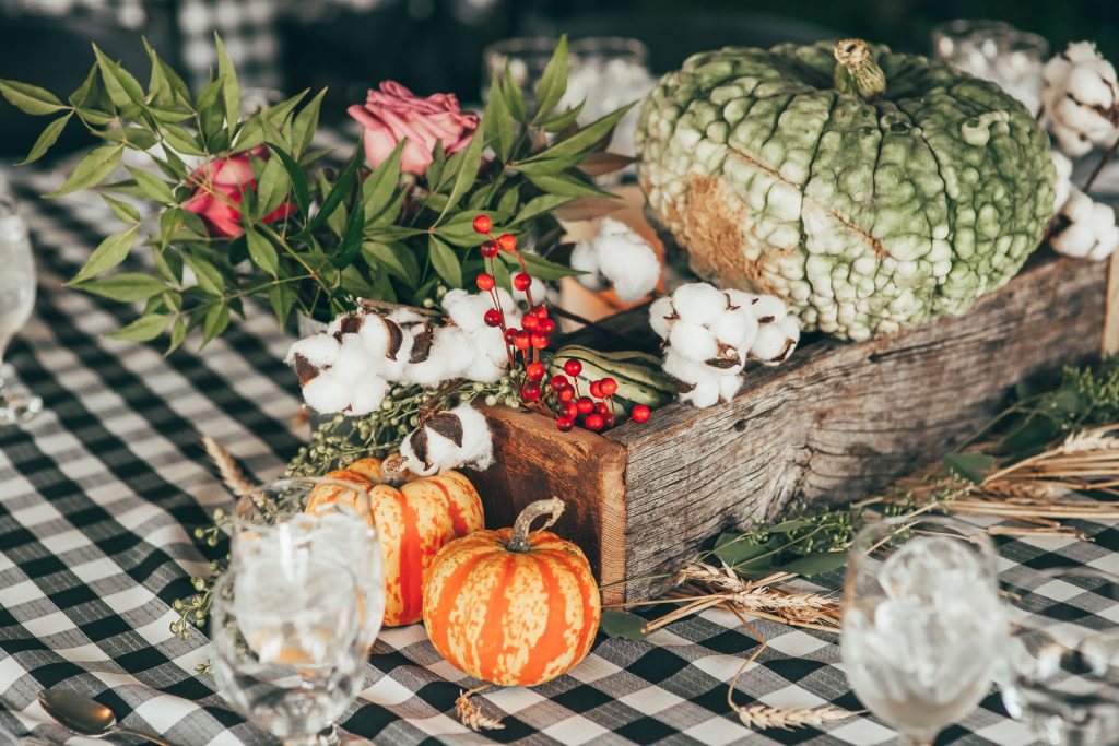 close up of fall centerpiece with wooden box and small pumpkins
