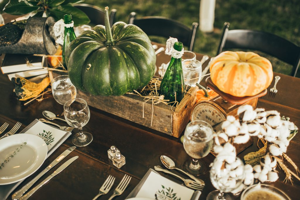 fall table centerpiece with green and orange pumpkins