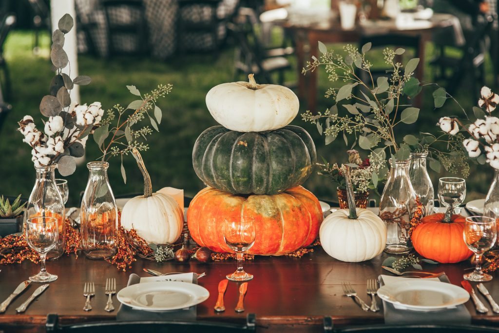 fall table vignette with lots of small pumpkins and greenery