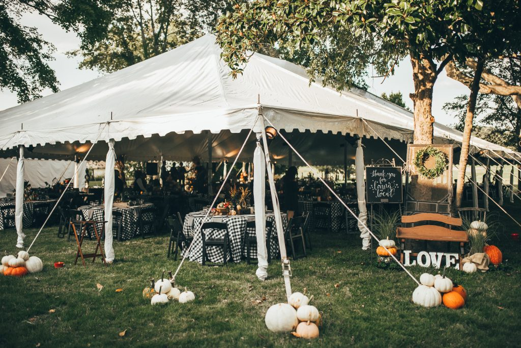 white tent over dinner tables decorated for fall