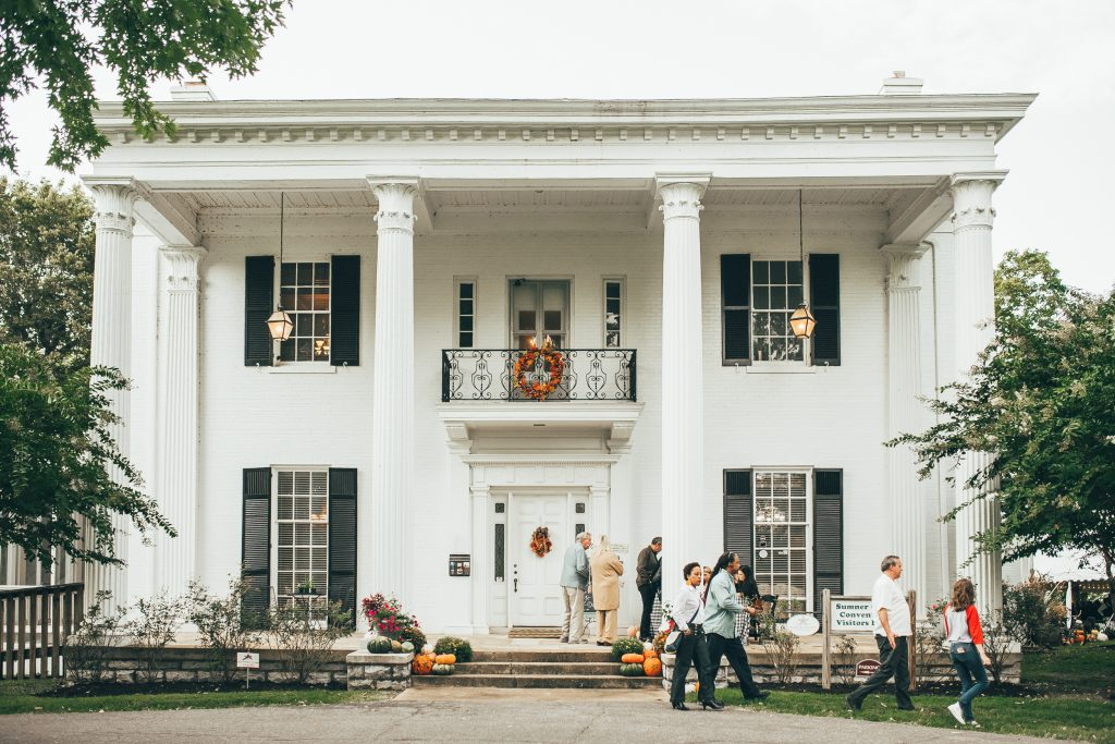 exterior of white home decorated for fall