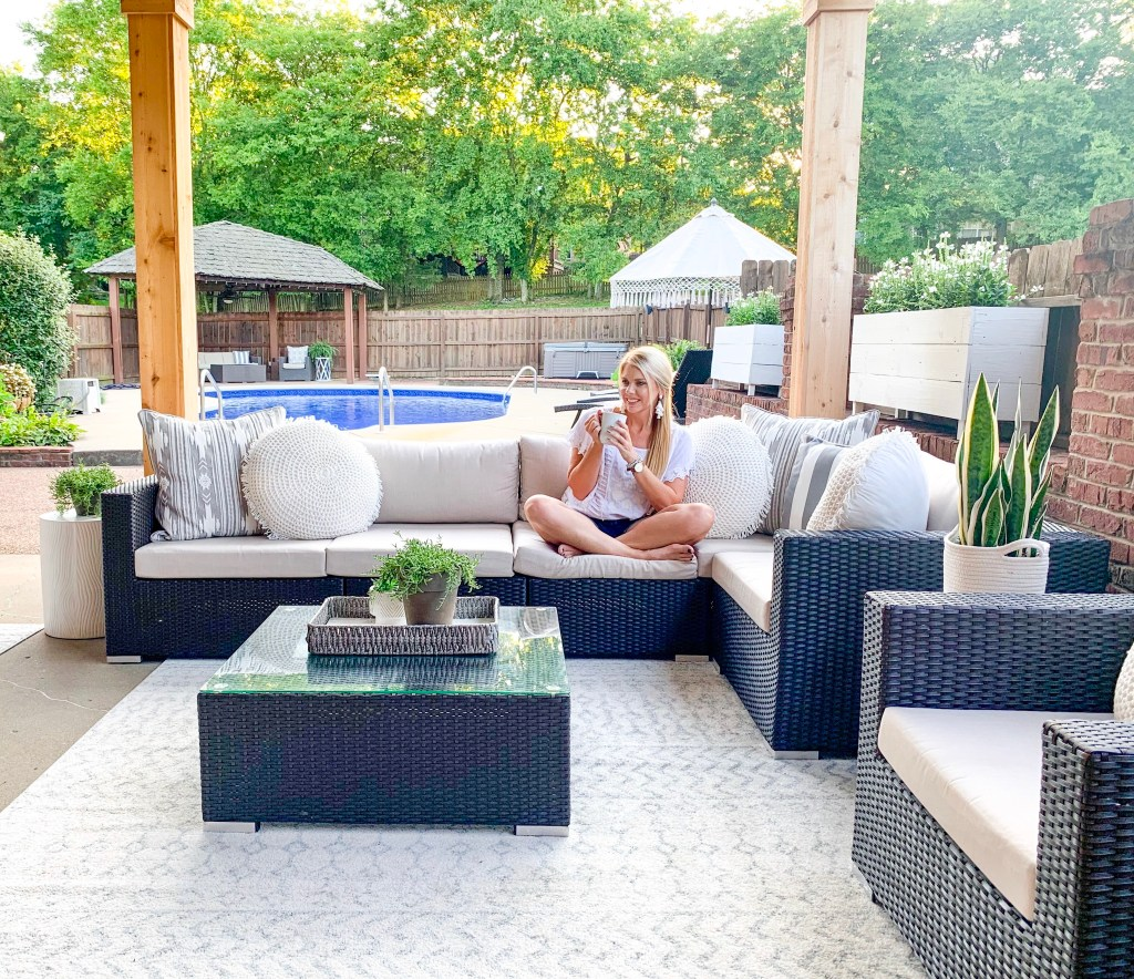 girl on outdoor sectional drinking coffee