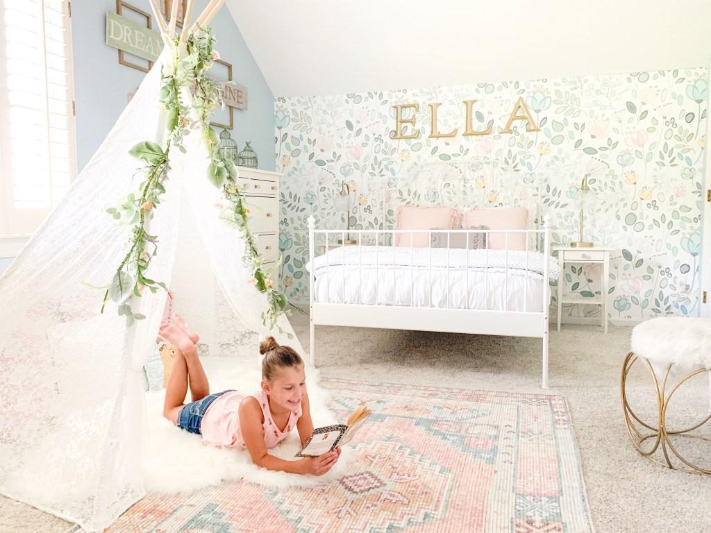 little girl reading on pink rug