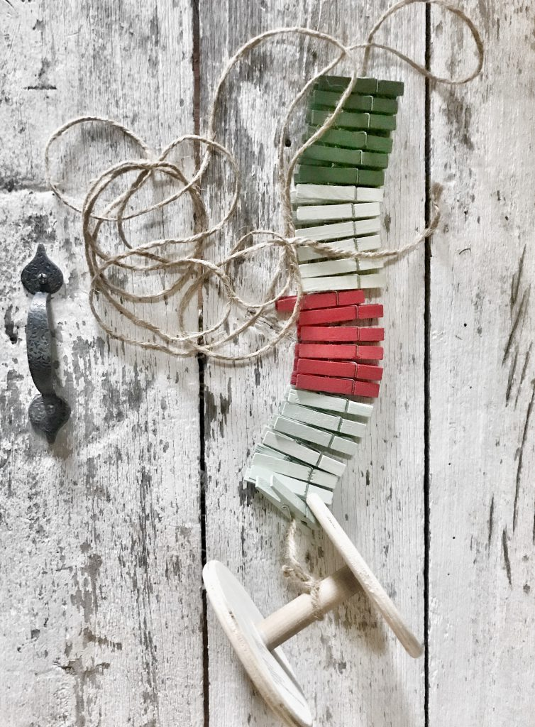 materials to create Christmas card holder, twine and red, white, and green clothespins