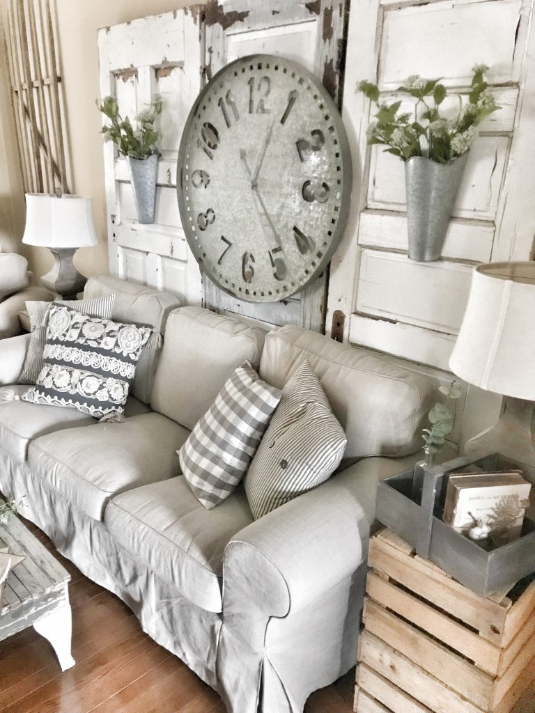 oversized galvanized wall clock hung on antique doors