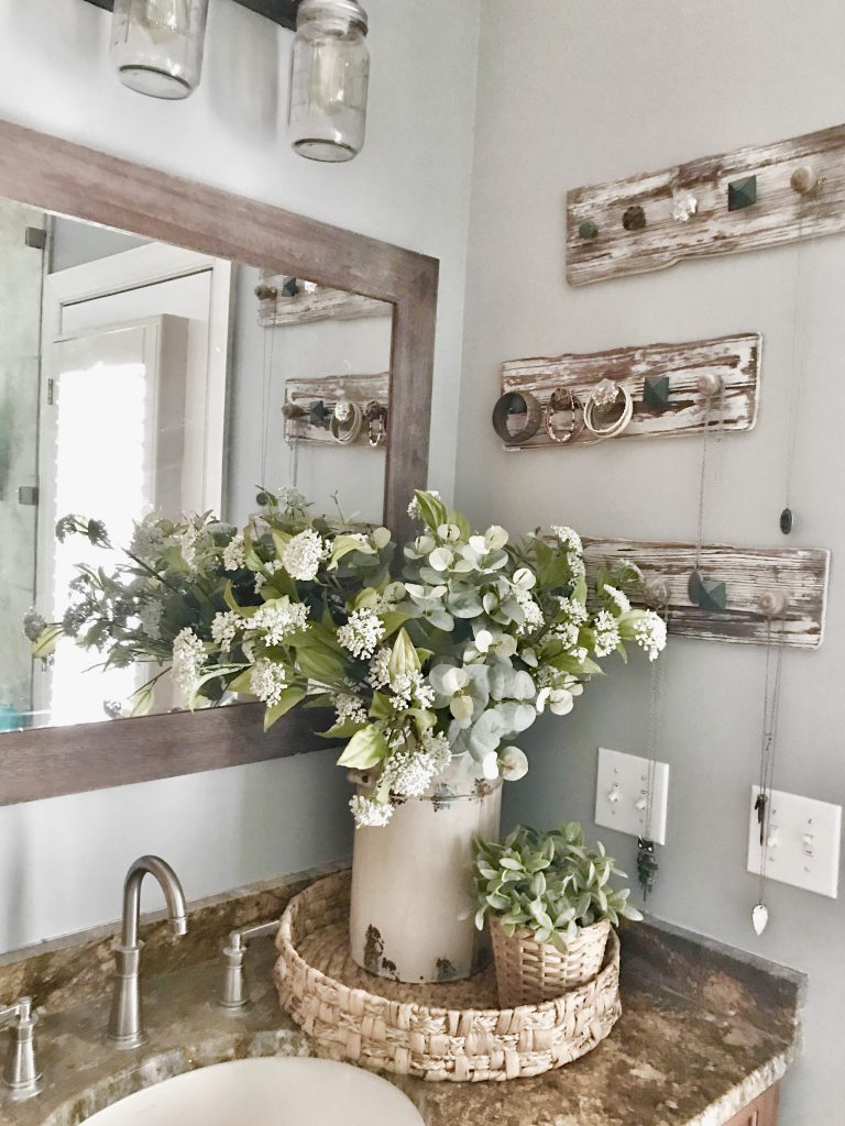 bathroom vanity with jewelry hanging on wooden pegs