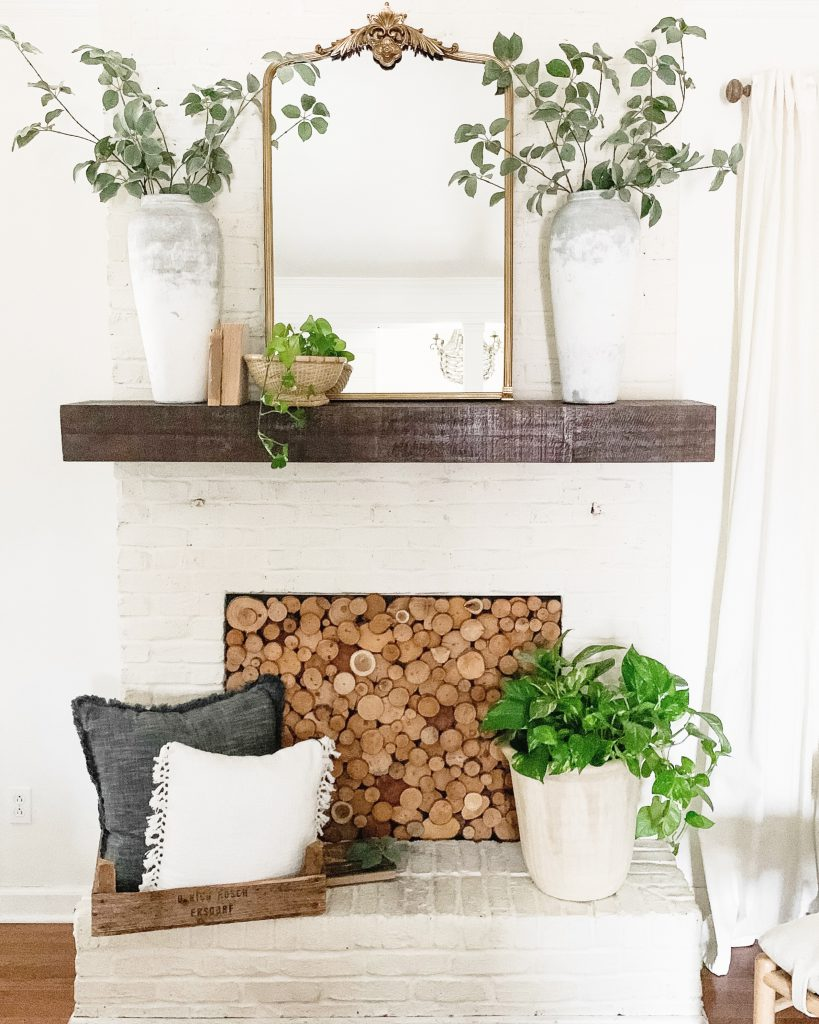 mantel with concrete pots and gold mirror
