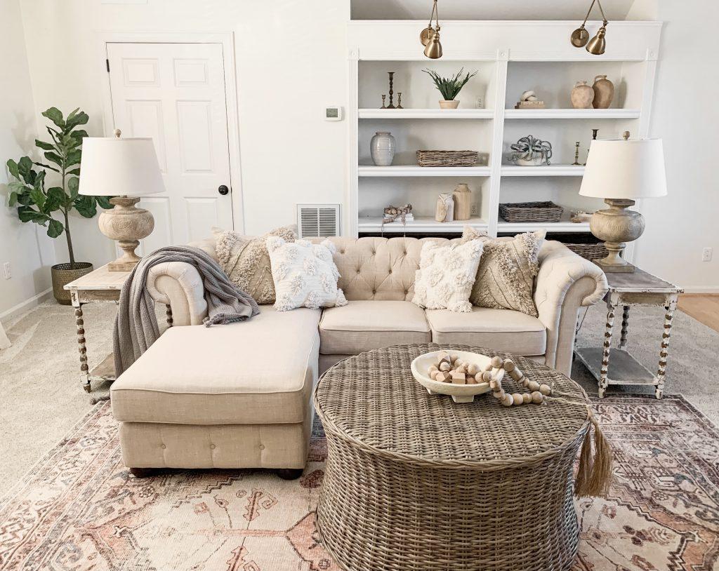 sofa in bonus room with built in book shelves