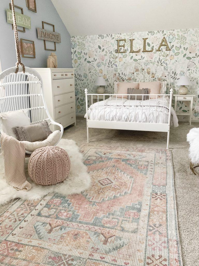white rattan swing chair in girl's room