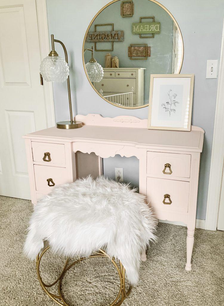 pink vanity with gold round mirror